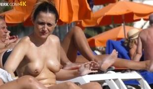 Pierced nipple chick spraying on sunscreen