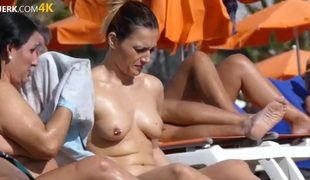 Pierced nipple on a topless tanning babe