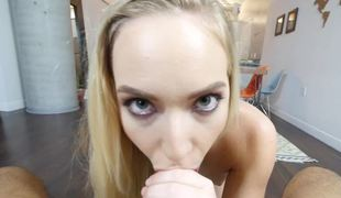 A blonde with a slim body is placing her face hole around a big dick to suck