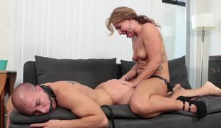 A girl is punishing her stud by fucking him with a big strap on