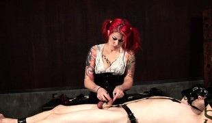 Dominatrix with flaming hair restrains her bound slave's dick and balls with chains